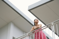 Woman standing on balcony, leaning on railing, looking away - Alex Mares-Manton