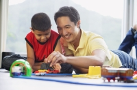 Father and son side by side on floor, playing with train set - Alex Mares-Manton