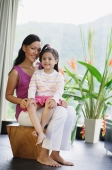 Mother with young girl on her lap, smiling at camera - Alex Mares-Manton