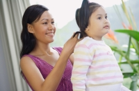 Mother tying hair of young daughter - Alex Mares-Manton