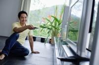 Man sitting on floor, pointing remote control at TV - Alex Mares-Manton