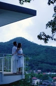 Couple standing on balcony, side view - Alex Mares-Manton