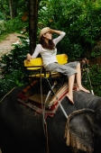 Young woman sitting on top of elephant, barefoot and wearing a hat, Phuket, Thailand - Nugene Chiang