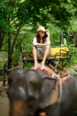Young woman sitting on elephant, looking at camera, touching hat, Phuket, Thailand - Alex Mares-Manton