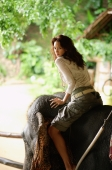 Young woman on elephant, looking over shoulder at camera, portrait, Phuket, Thailand - Nugene Chiang