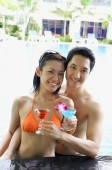 Couple in swimming pool holding cocktail drinks, smiling at camera - Alex Mares-Manton
