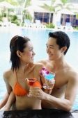 Couple in swimming pool holding cocktail drinks, smiling at each other - Alex Mares-Manton