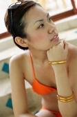 Young woman in orange bikini, hand on chin, looking away - Nugene Chiang