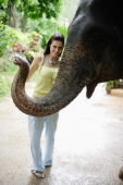 Young woman posing with elephant, looking at camera, Phuket, Thailand - Alex Mares-Manton