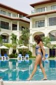 Woman in swimwear, walking next to swimming pool, building in the background - Alex Mares-Manton