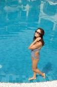 Woman in swimwear, wearing sunglasses, hand on head, walking at edge of swimming pool - Alex Mares-Manton