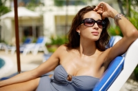 Woman in swimwear, wearing sunglasses, sitting on deck chair, hand on head - Alex Mares-Manton
