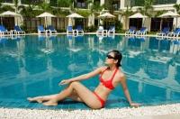 Woman sitting next to swimming pool, wearing bikini - Alex Mares-Manton