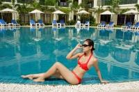 Woman sitting next to swimming pool, adjusting sunglasses - Alex Mares-Manton