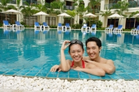 Couple in swimming pool, smiling at camera - Alex Mares-Manton
