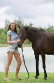 Woman standing with horse, smiling at camera - Alex Mares-Manton