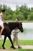 Woman on horse, man walking beside her - Alex Mares-Manton
