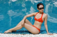 Woman sitting next to swimming pool, wearing red bikini - Alex Mares-Manton