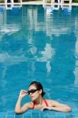 Woman leaning on edge of swimming pool, adjusting sunglasses - Alex Mares-Manton