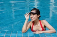 Woman leaning on edge of swimming pool, adjusting sunglasses, smiling - Alex Mares-Manton