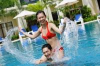 Couple in swimming pool, woman sitting on mans shoulders, splashing water - Alex Mares-Manton