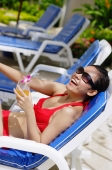 Woman in bikini, sitting on deck chair, holding drink, smiling - Alex Mares-Manton