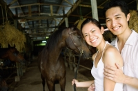 Couple in stable, standing with horse, looking at camera - Alex Mares-Manton