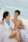 Couple sitting on yacht, side by side, man holding drink - Alex Mares-Manton