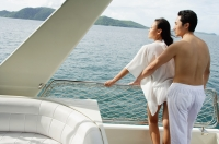 Couple standing on stern of yacht - Alex Mares-Manton