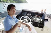 Man sitting at helm of yacht, looking at camera - Alex Mares-Manton