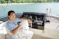 Man sitting at helm of yacht, portrait - Alex Mares-Manton