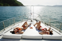 Women sunbathing on boat deck - Alex Mares-Manton
