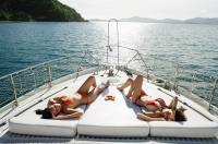 Women sunbathing on boat deck - Alex Mares-Manton