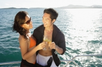 Couple on boat, holding champagne glasses, toasting - Alex Mares-Manton