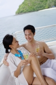 Couple sitting on stern of yacht, with champagne glasses - Alex Mares-Manton