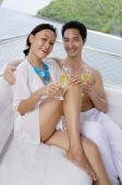 Couple sitting on yacht, holding champagne glasses, smiling at camera - Alex Mares-Manton
