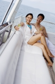 Couple lounging on yacht, holding champagne glasses - Alex Mares-Manton