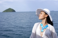 Woman wearing white hat, in profile, ocean behind her - Alex Mares-Manton