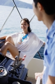 Couple on yacht, man steering, woman sitting and smiling at him - Alex Mares-Manton