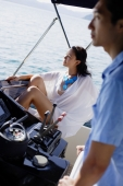 Couple on yacht, man steering, woman sitting and looking away - Alex Mares-Manton