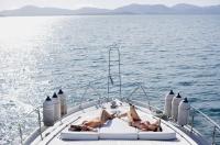Women sunbathing on boat deck, high angle view - Alex Mares-Manton