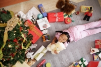Girl lying on floor, surrounded by presents, holding teddy bear, looking at camera - Alex Microstock02