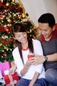 Couple sitting next to Christmas tree, man giving woman gift - Alex Microstock02