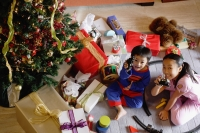 Children with opened Christmas presents, showing toys to camera - Alex Microstock02
