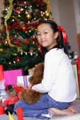 Girl sitting next to Christmas tree, holding teddy bear, looking at camera - Alex Microstock02