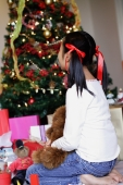 Girl sitting next to Christmas tree, rear view - Alex Microstock02