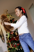 Girl standing next to Christmas tree, holding stuffed toy - Alex Microstock02