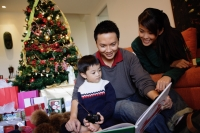 Family with one child, looking at book, Christmas tree behind them - Alex Microstock02