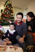 Family with one child, sitting by Christmas tree, smiling - Alex Microstock02