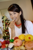 Woman eating a cookie, holding plate of food - Alex Microstock02